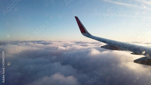 View from the porthole of an airplane. Flying at high altitude over an even layer of clouds. Early morning. - 290655149