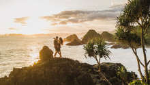 Couple Enjoying Sunset With Amazing Ocean And Mountain View. Travel Concept, Panoramic Shot, Wanderlust.