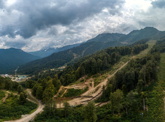 Fototapeta na wymiar construction of a ski slope on a mountainside covered with forest. Cloudy summer day, aerial view