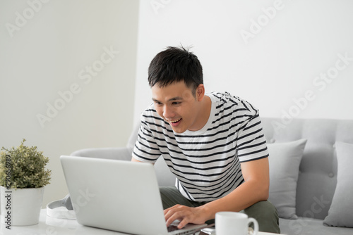 Fotografía  Young handsome man sitting with laptop in living room and smiling