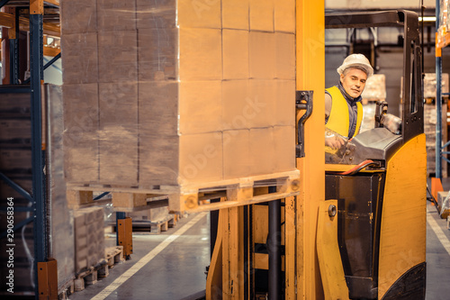 Fotografie, Obraz  Kind grey-haired male person working on warehouse