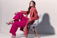 High Fashion Portrait Of Young Elegant Woman. Coral Coat, Magenta Pants, White Blouse.