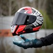 canvas print picture - Hand magically holds a motorcycle sports helmet. Close up. Hand in a leather glove