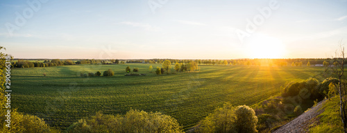 Tuinposter Wit Beautiful sunset at summer day. Amazing nature landscape. View from the top of the hill. Green fields and trees.