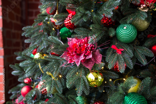 Green Christmas tree decorated with Christmas gifts and a garland. New Year.
