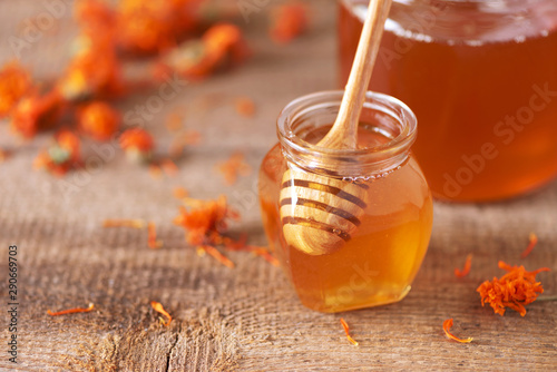 Herbal honey in jar with dipper, honeycomb, bee pollen granules, calendula flowers on grey background.