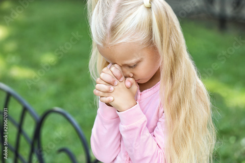 Cute little girl praying outdoors Canvas Print
