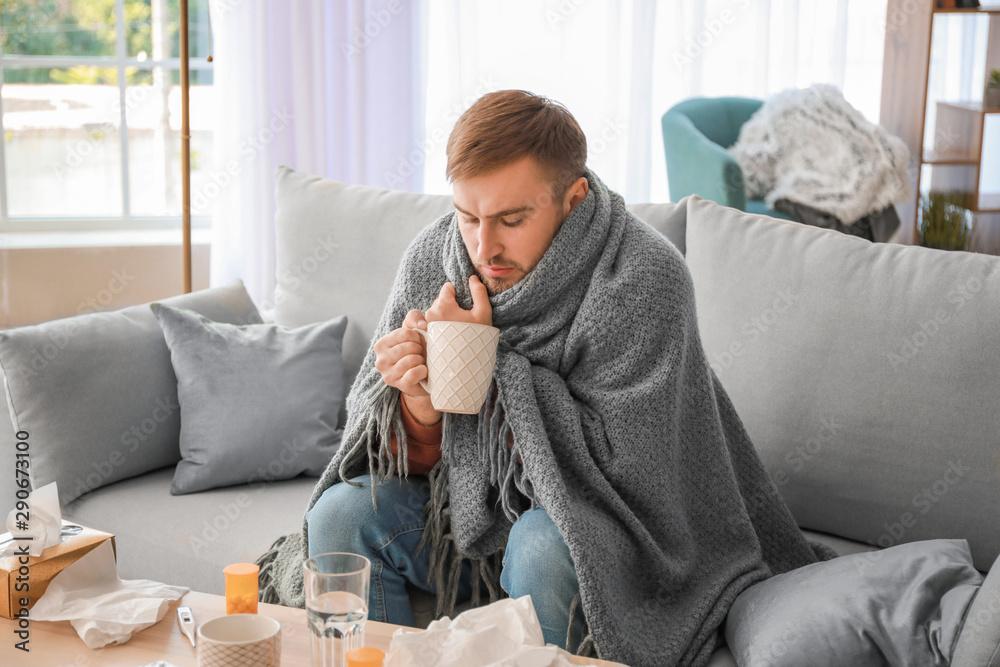 Fototapeta Sick man drinking hot tea at home