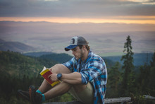 Young Caucasian Man Reading Book On Top Of The Mountain.