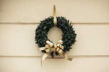 Christmas Street Decor. Stylish Christmas Wreath With Golden Bow On Wall Of Old Building At Holiday Market In City Street. Space For Text. Modern  Decoration