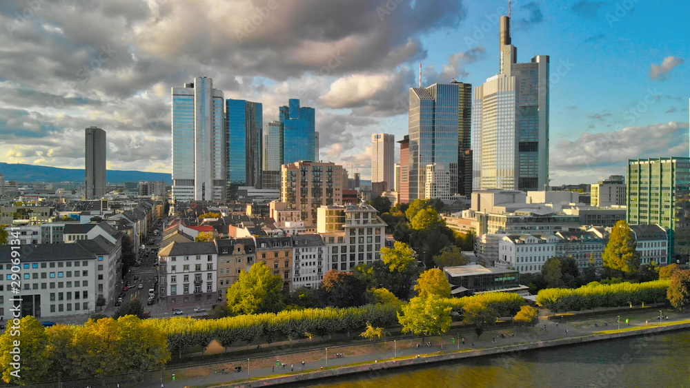 Fototapeta Aerial flying along the futuristic skyline the business and financial centre of Frankfurt am Main, sunset view from drone
