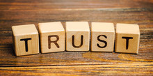 Wooden Blocks With The Word Trust. Trust Relationships Between Business Partners, Friends, Relatives. Respect And Authority. Confidence In A Person. Reliable Partner