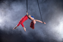 Female Athletic, Sexy And Flexible Aerial Circus Artist With Redhead On Aerial Straps On Black Background