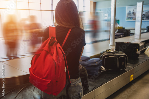 Fotografie, Obraz  A girl with a red backpack is waiting for her luggage at the airport