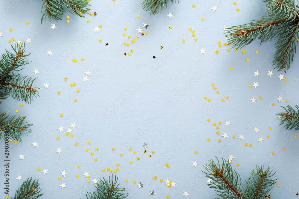 Fototapeta Blue Christmas background with fir tree branches and glitter confetti stars. Christmas, New Year, winter holidays concept. Xmas frame, banner mockup.