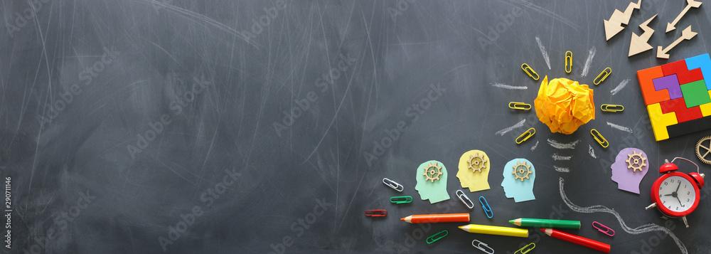 Fototapeta Education concept image. Creative idea and innovation. Crumpled paper as light bulb metaphor over blackboard