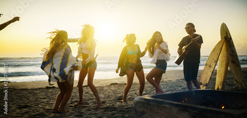 Fototapeta  multiethnic group of californians dancing around fire pit on beach