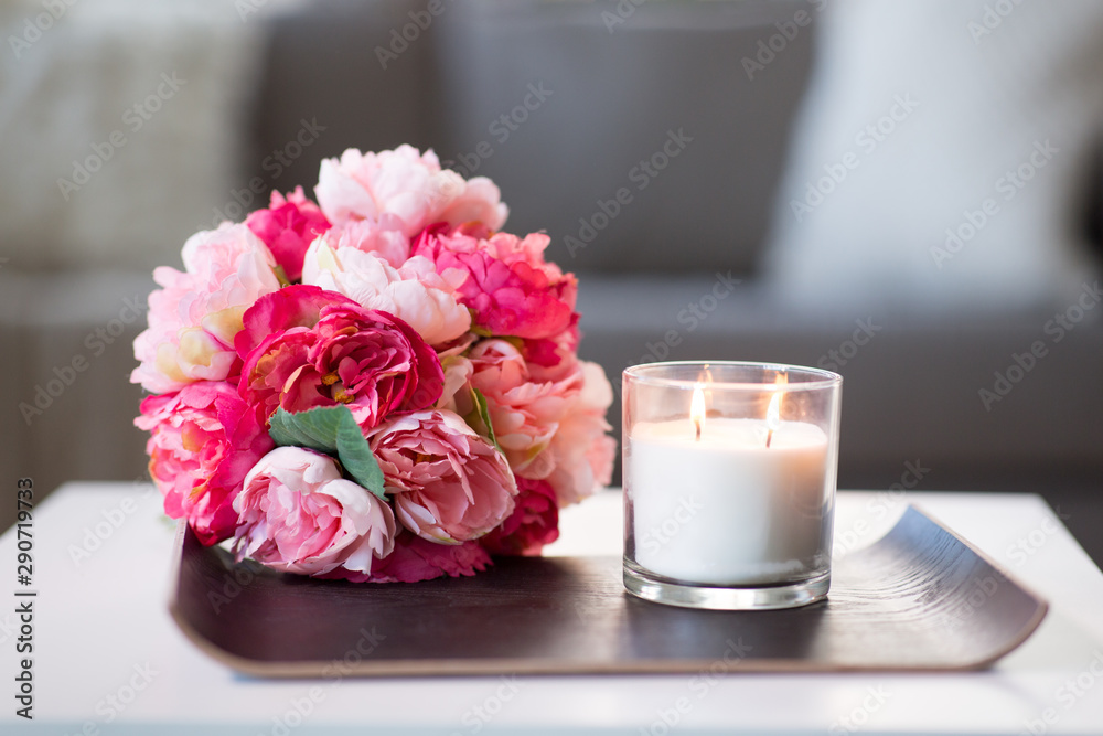Fototapeta decoration, hygge and cosiness concept - burning fragrance candle and flower bunch at cozy home