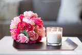 decoration, hygge and cosiness concept - burning fragrance candle and flower bunch at cozy home