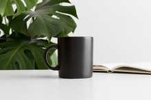 Black Mug Mockup With A Notebook On A White Table And A Monstera Plant.