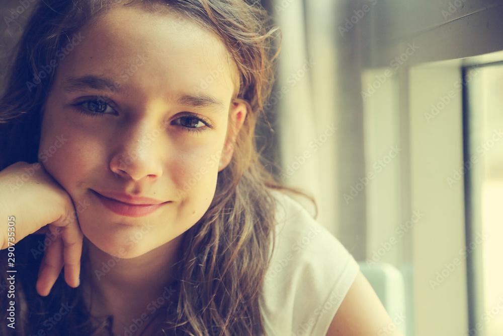 Fototapeta Teenage girl is sitting indoor in urban cafe. Casual portrait of teenager girl. Toned.