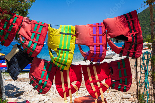 Printed kitchen splashbacks Fairytale World Colorful life jackets hanging on the beach, water safety concept.