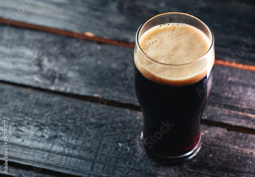 Photo A glass of dark craft beer porter on a wooden table in a pub with copyspace