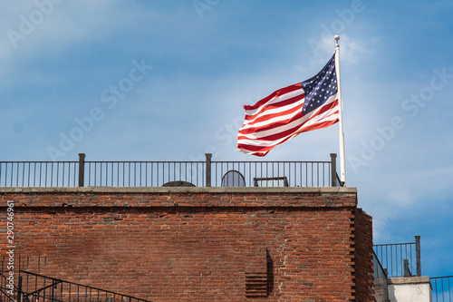american flag in front of building wind summer daylight glory power freedom wavi Wallpaper Mural