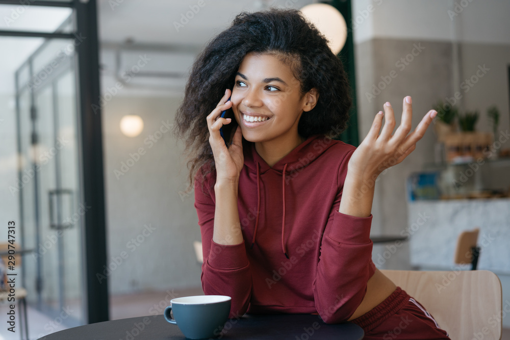 Fototapeta Cheerful African American woman talking on mobile phone, sitting in modern cafe. Authentic portrait of beautiful curly haired hipster girl holding smartphone, laughing, communication
