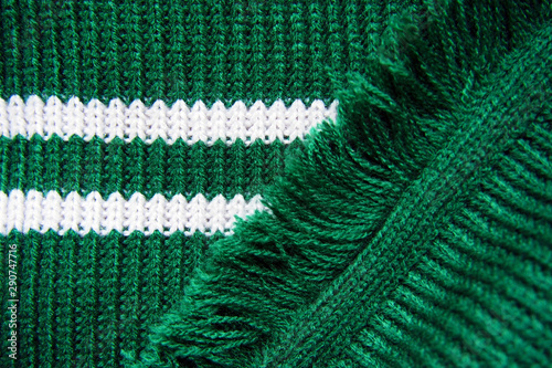 Foto Knitted texture of green warm scarf with white stripes and fringe