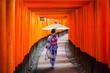 Leinwanddruck Bild - Woman in traditional kimono and umbrela walking at torii gates, Japan