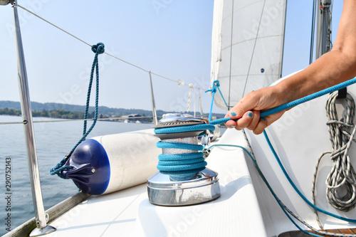 Pinturas sobre lienzo  Hand of a skipper girl pulls a blue rope