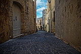 Fototapeta Uliczki - Narrow Street with High Surrounding Walls