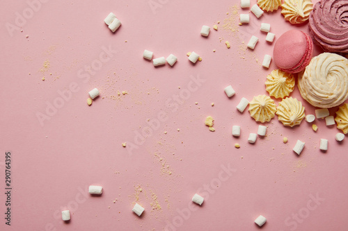 Aluminium Prints Macarons Top view of sweet pink macaroons, meringues and marshmallows with yellow pieces on pink background