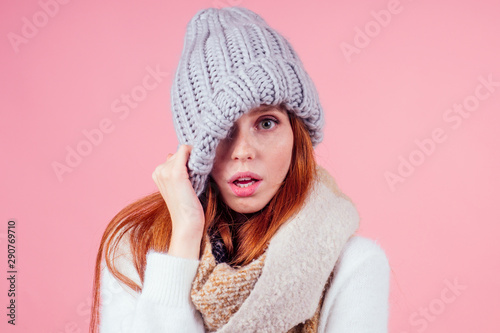 shy redhead ginger woman putting a knitted spiky hat on his head,hiding eye and Wallpaper Mural