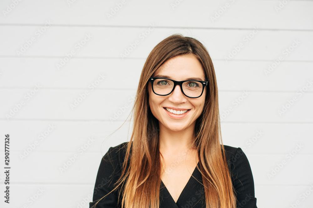 Fototapeta Close up portrait of beautiful young businesswoman wearing eyeglasses