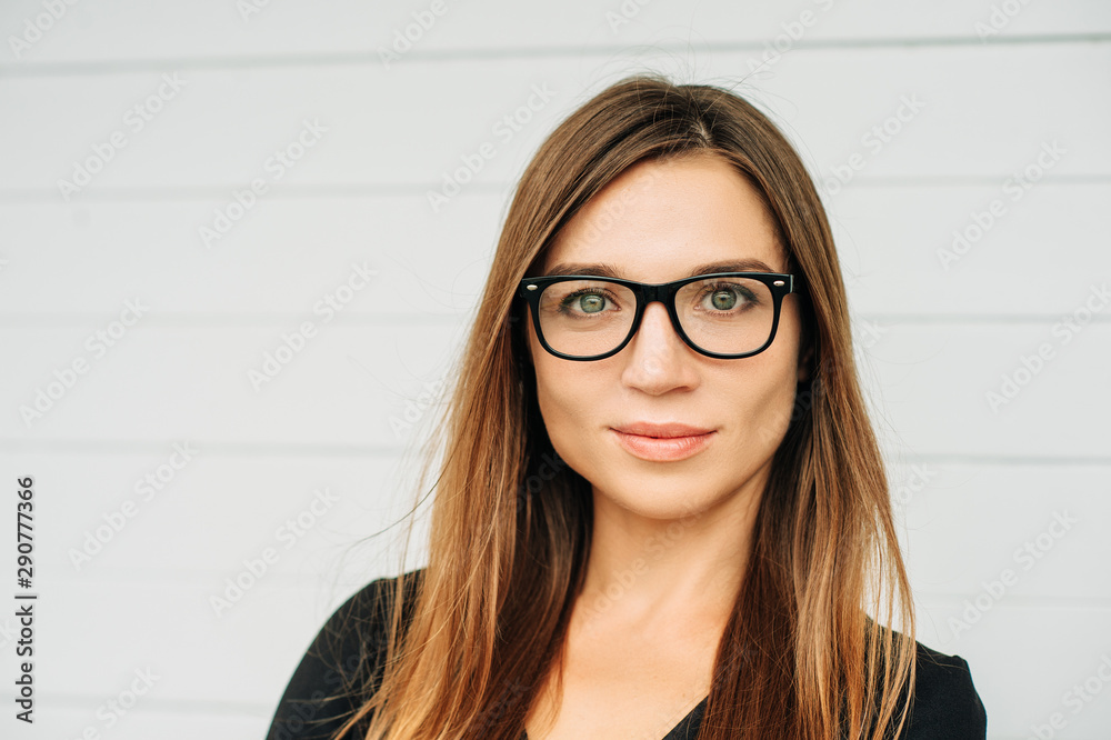 Fototapeta Close up portrait of beautiful young businesswoman wearing eyeglasses