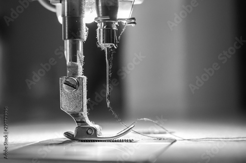 Fototapeta Close-up needle of white industrial sewing machine use sew cloth with black and white tone (monochrome)
