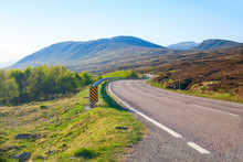 Winding  Road Through The Scottish Highlands In The Morning, United Kingdom. Typical Scottish Mountain Landscape In Spring.