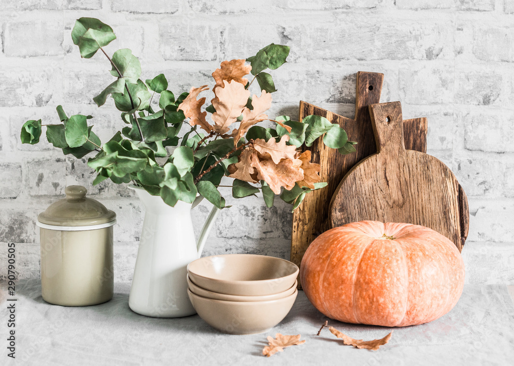 Fototapety, obrazy: Kitchen autumn still life. Dishes, cutting boards, pumpkin on the table, on a light background. Rustic cozy style