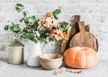 Kitchen Autumn Still Life. Dishes, Cutting Boards, Pumpkin On The Table, On A Light Background. Rustic Cozy Style