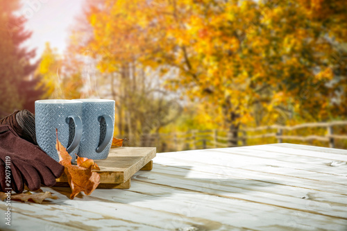 Foto auf AluDibond Honig Autumn background with white wooden table board and mug on it. Blurred colourful trees view in distance.