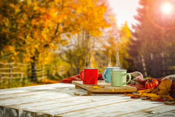 Autumn background with white wooden table board and mug on it. Blurred colourful trees view in distance.