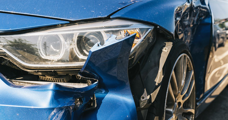 Car crash or accident. Front fender from a blue car and light damage and scratchs on bumper. Broken vehicle detail or close up.