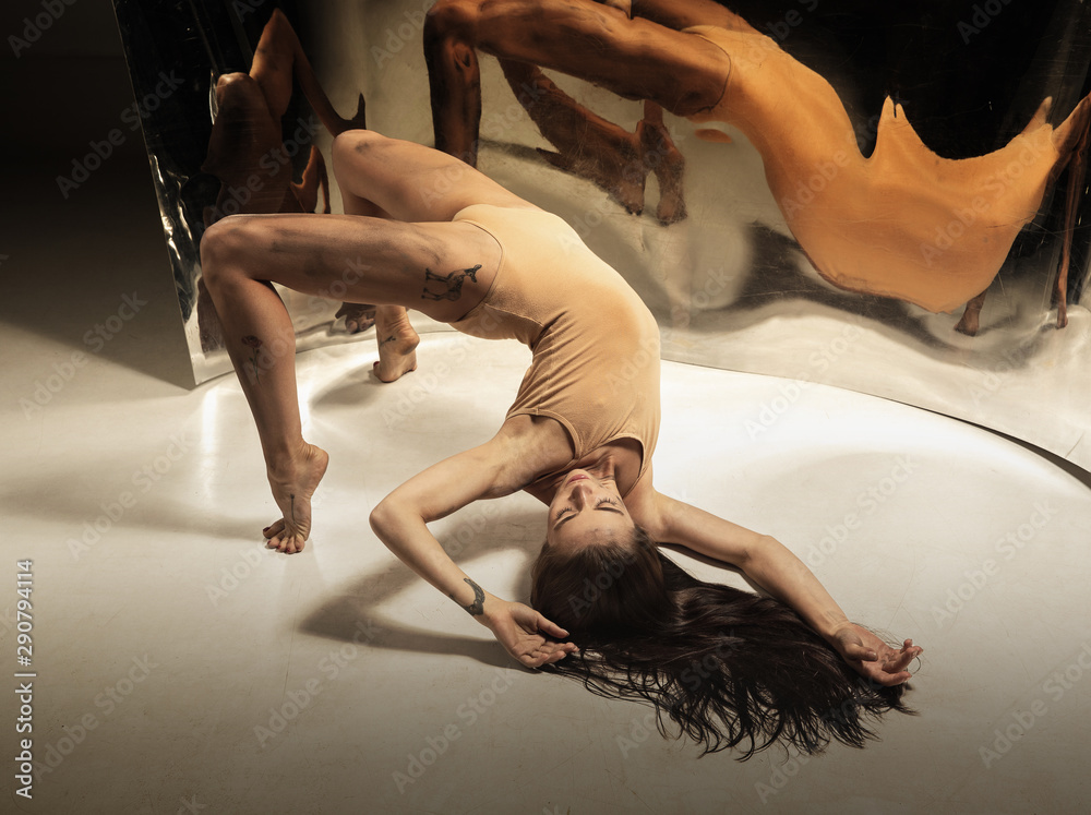Fototapety, obrazy: Weightless. Young, stylish modern ballet dancer on brown background with mirror, illusion reflections on surface. Magic of flexibility and motion. Concept of creative art dancing, action and inspiring