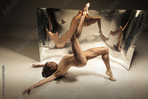 Inspired. Young, stylish modern ballet dancer on brown background with mirror, illusion reflections on surface. Magic of flexibility and motion. Concept of creative art dancing, action and inspiring.