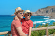 Dad and son in sun hats and sunglasses and similar clothes standing on cliff against wonderful sea view. They smiling and enjoying their summer vacations.