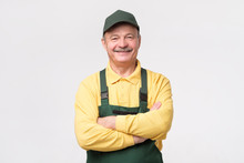 Hispanic Mature Mechanic In Green Cap And Overalls Standing With Folded Handssmiling On White Background.