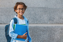 Portrait Of Happy Caucasian Young School Boy With Backpack Holding Notebook Outside The Primary School