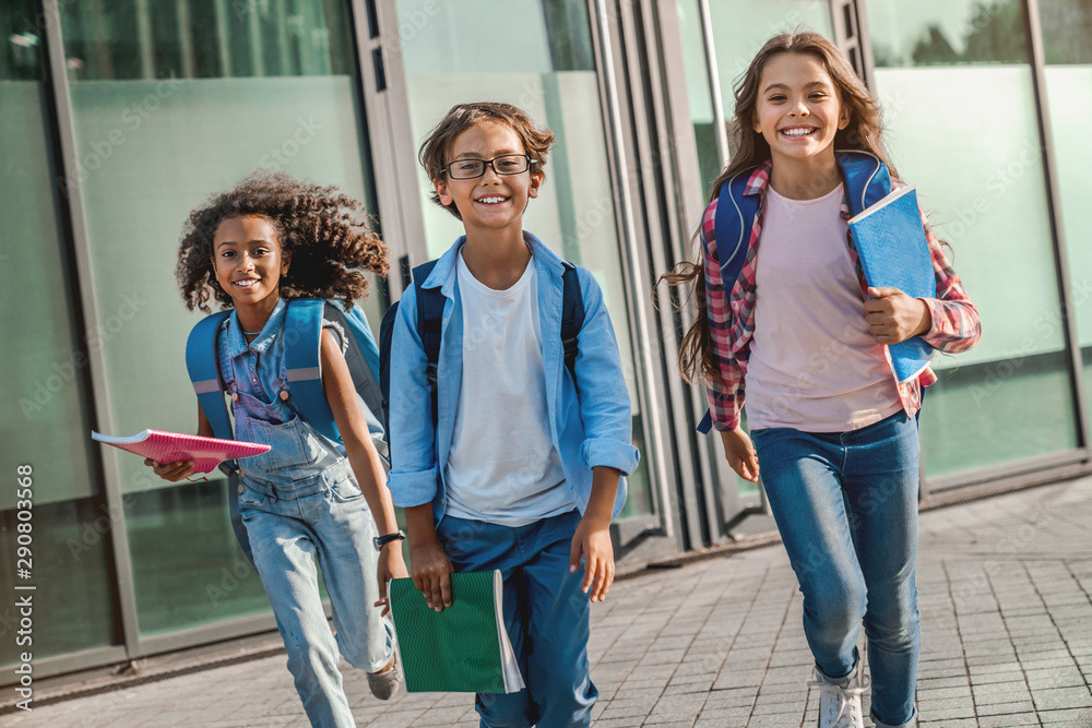 Fototapety, obrazy: Group of elementary school kids rushing out from school